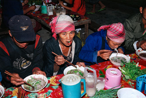 Tribal people eating in the market at Muang Sing, Luang Namtha Province.