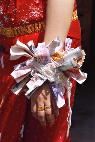 Hand of a young bride bequeathed with financial offerings at Muang Sing, Luang.