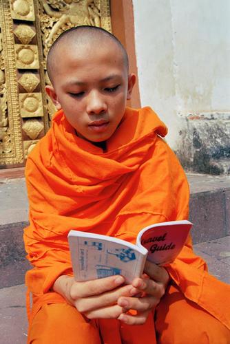 Young monk reading a book at the Wat Thammothayalan temple complex, Mount Phousi, Luang Prabang.