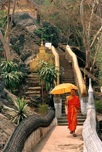 Monk with parasol walking along a balustrade in the Wat Thammothayalan temple complex, Mount Phousi, Luang Prabang.