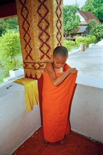Young monk putting on his robe, Luang Prabang.