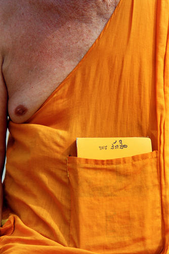 Monk with prayer book in his robe pocket at the Wat Thammothayalan temple complex, Mount Phousi, Luang Prabang.