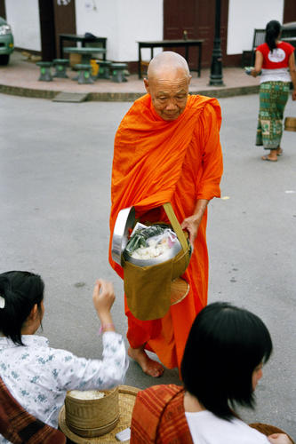 Old monk collecting his early morning alms, Luang Prabang.
