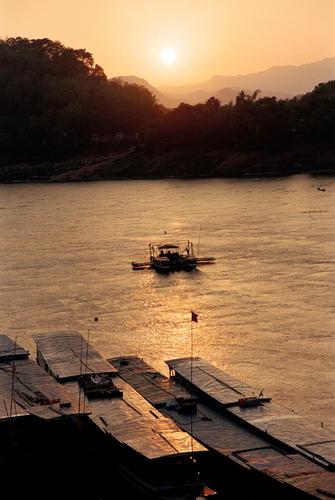 Sun setting over long boats on the Mekong River, Luang Prabang.
