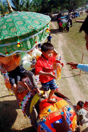 Young child being helped off an elephant at the annual Elephant Festival held in Sayaboury Province.