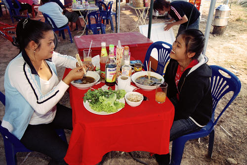 Two girls enjoying a meal at the annual Elephant Festival, Sayaboury Province, Laos.