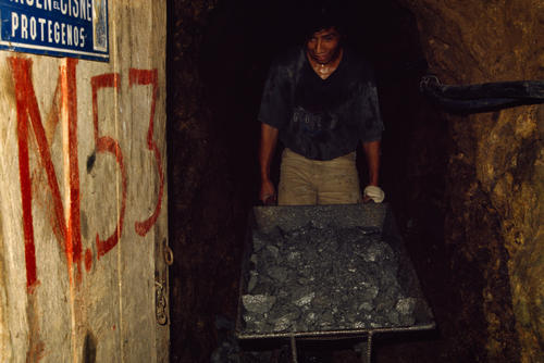 Miner collecting rock in a mine tunnel.