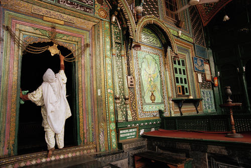 Lady ringing a bell at the entrance to the Khangar Shah Hamdan Mosque in Srinagar, Kashmir in India