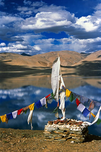 Prayer flags and a mani stone located on the shore of Lake Tso-Moriri in Korzok, Ladakh, India