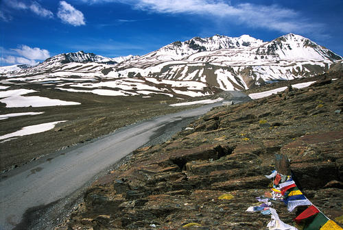 Prayer flags mark the breathtaking approach to the Baralacha La Pass with a row of snowy mountains to the south.