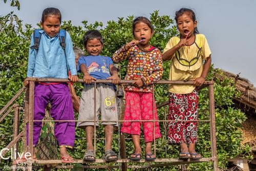 Tharu children brushing their teeth outside of the Bardia National Park