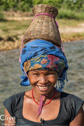 Tharu woman with a traditional fishing pot on her head outside of the Bardia National Park