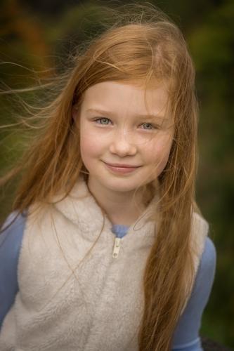 Ģimenes fotosesija bērnu foto meitene ar rudiem vējā izspūrušiem matiem