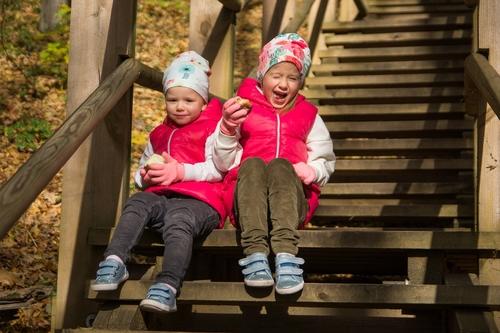 Ģimenes fotosesija bērni sēž uz trepēm saulainā rudens dienā rozā jakās ēd ābolus