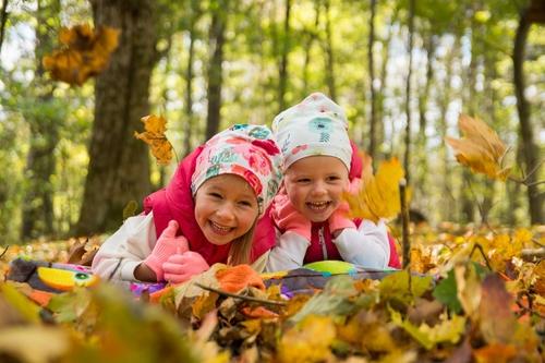 Bērnu fotosesija dzeltenās rudens lapās saulainā mežā parkā