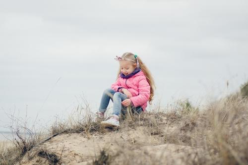 Ģimenes fotosesija ziemā pie jūras sēžot kāpās rozā jakā