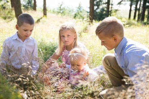 Bērnu fotosesija sēžot smilgu pļavā saulainā vasaras dienā četri bērni