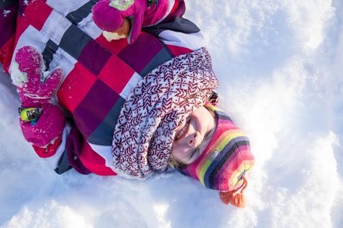 Bērna fotosesija ziemā guļot sniegā un smejoties rozā jakā latviskā šallē