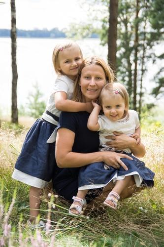 Ģimenes foto smilgu pļavā ar ezeru fonā saulainā dienā vienādās kleitās