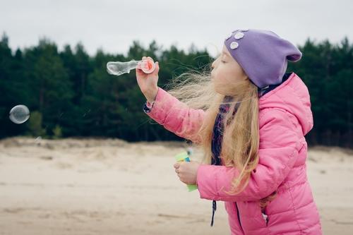 Bērna fotosesija rudenī pie jūras jakā un cepurē pūšot burbuļus