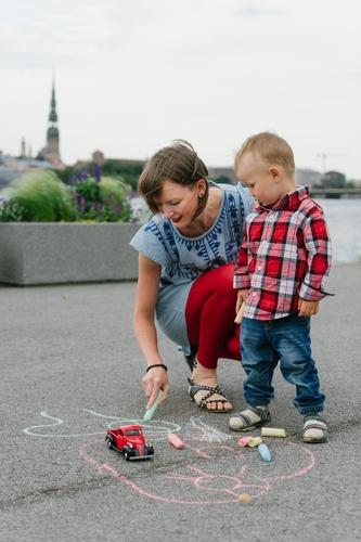 Ģimenes fotosesija ar Pēterbaznīcas torni fonā mamma zīmē uz asfalta bērns rūtainā kreklā skatās