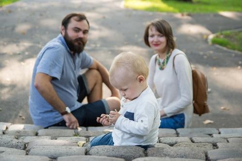 Ģimenes fotosesija uz trepēm bērns sēž priekšplānā vecāki fonā uz pakāpiena