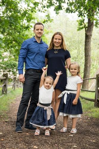 Saskaņoti tērpi ģimenes fotosesijā zilas un baltas kleitas meitām