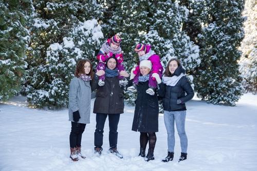 Ģimenes fotosesija ziemā apsniguši koki fonā vecāki un bērni ziemas jakās