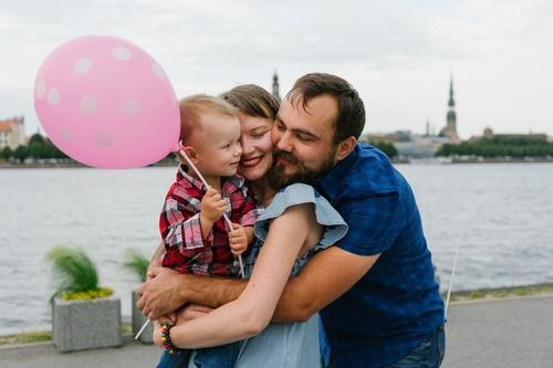 Ģimenes fotosesija uz AB dambja ar skatu uz Vecrīgu un Daugavu vecāki apskauj bērnu