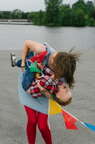 Ģimenes fotosesija lietainā dienā pie ūdens košas drēbes un sarkani tērpi