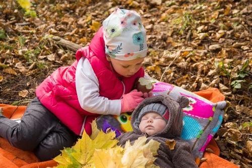 Lielā māsa pieskata bēbīti rudens fotosesija mežā