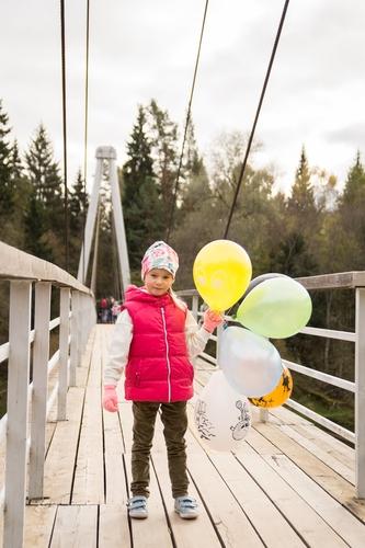 Bērna fotosesija meitene uz tilta ar krāsainiem baloniem rokās