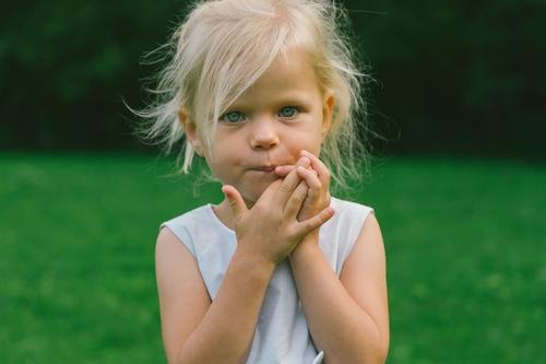 Maza meitene izspūrušiem matiem baltā kleitiņā bērna fotosesija