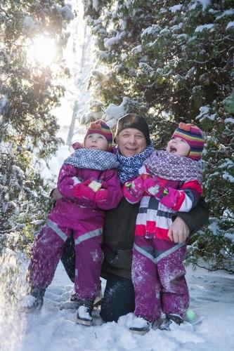 Sniegota fotosesija ģimenei saulainā aukstā laikā rozā kombinzonos