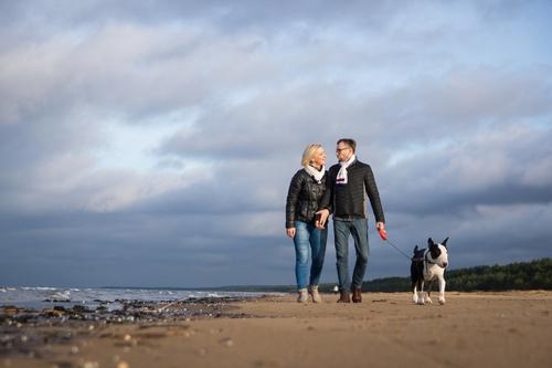 pāris ar suni pastaigājas gar jūras krastu rudenī ziemā fotosesijā