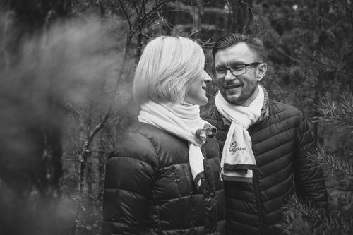 pāris melnbaltā foto ziemas jakās šallēs fotosesija rudenī