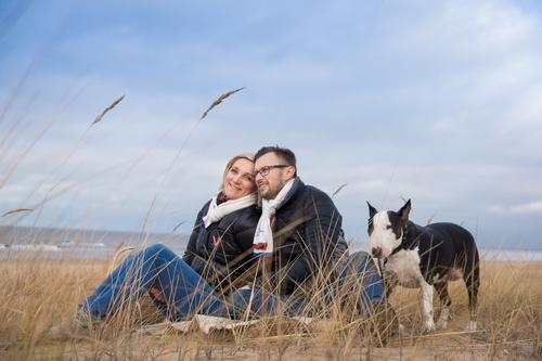 pāris ar suni sēž kāpās pie jūras rudenī fotosesijā