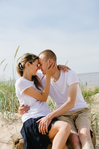 apskāvies pāris kāpās pie jūras saulainā laikā ar pierēm kopā fotosesija
