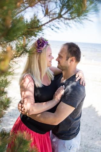 Pāris apskāvies kāpās zem priedes vasarīga fotosesija