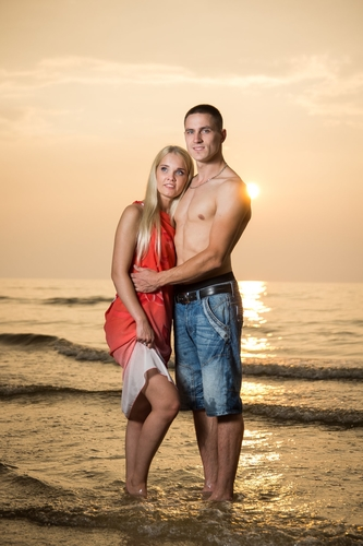 meitene sarkanā kleitā kopā ar puisi jūras krastā ūdenī saulrietā fotosesijai