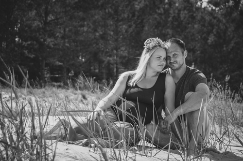pāris sēž zālēs kāpās romantiska melnbalta fotorāfija