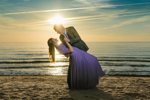 sapucējies pāris dejo jūras krastā fotosesija saulrietā