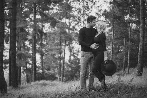 pāris meža pļavā melnās drēbēs melnbaltā fotosesija