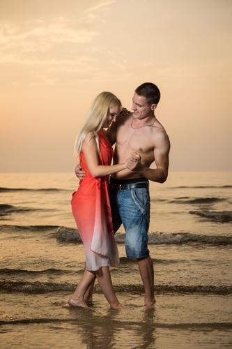 pāris dejo jūras krastā saulrieta fotosesijā