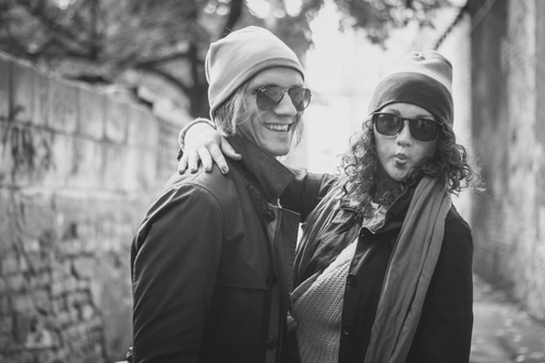 jauns pāris ākstās smejās ar saulesbrillēm cepurēm un šallēm pāra fotosesija