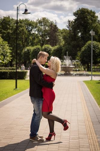 jauns pāris sarkanā kleitā uzvalkā apķērušies Ziedoņdārzā saulainā fotosesijā