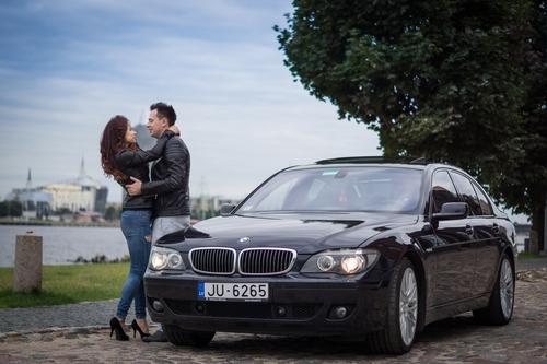 Jauns pāris uz Vecrīgas fona stāv pie automašīnas bmw ādas jakās fotosesija pārim