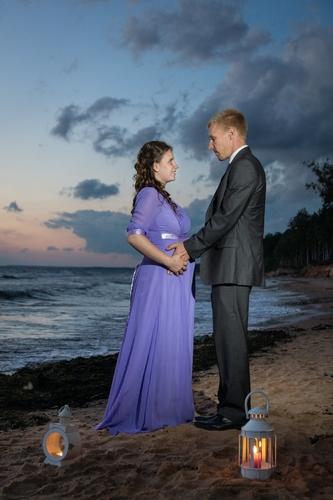 Gaidību fotosesija saulrietā pie jūras ar zibspuldzi grūtniece garā kleitā vīrs uzvalkā svinīgi