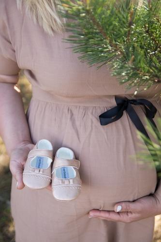 Topošā māmiņa tur mazuļa kurpītes un punci