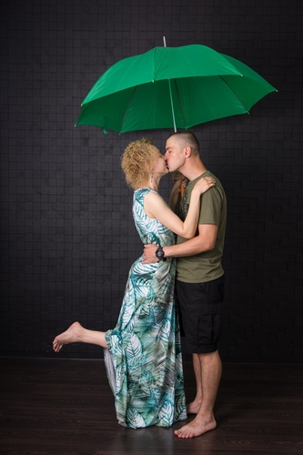 pāris skūpstās zem liela lietussarga ar paceltu kāju uz melna fona foto studijā